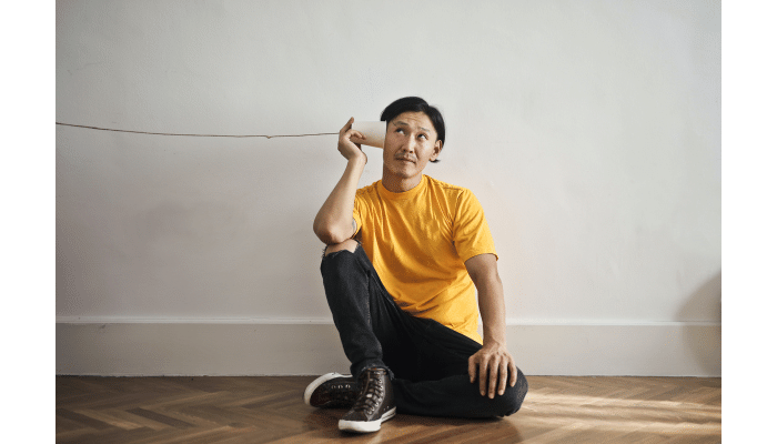 man-in-yellow-shirt-with-cup-on-string-telephone
